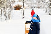 Adorable little girl and cute boy outdoors on beautiful winter day having fun playing in snow poster