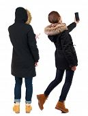 Back view of two young woman photographed on a mobile phone in winter jacket. Rear view people colle poster