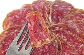 primer plano de un montón de rodajas de salchichón, salami español y un tenedor