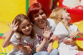 foto of bouncing  - Young mother with her cute daughters waving you laughing on the bouncing castle outdoors in a bright sunny day - JPG