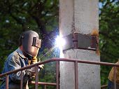 stock photo of collier  - The welder welds a metal plate of a pile