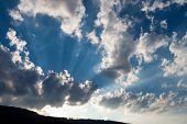 Sunbeam On The Blue Sky With A Dark And White Clouds. Sun Rays. Sunlight. Divine Light And Sky. Sunn poster
