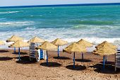 empty deck chairs on a sandy beach by the sea in spain.
