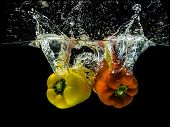Yellow and orange peppers, splashing in water