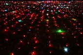 Rows Of Shiny Red Lamps On Ground Covered With Lush Grass. Lawn Illuminated With Shiny Colorful Ligh poster