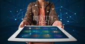 Young business person working on tablet and shows the digital sign: IDENTITY THEFT poster