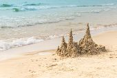 Sand House Or Sandcastle With Towers Built Of Wet Sand On Seashore Of Light Sandy Beach Near Turquoi poster