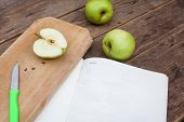 stock photo of sorbet  - Green apples on wooden table cutted for apple sorbet with book - JPG