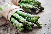 stock photo of vegetarian meal  - Bunch of fresh asparagus on wooden table - JPG