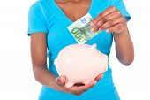Black African American Woman Inserting A Euro Bill Inside A Smiling Piggy Bank Isolated On White Bac