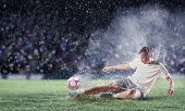 stock photo of wet feet  - football player in white shirt striking the ball at the stadium under the rain - JPG