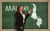 Teacher Showing Map Of Malawi On Blackboard