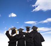 stock photo of graduation gown  - four graduate students and friends looking at sky - JPG