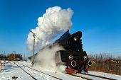 foto of loco  - Vintage steam train puffing through countryside during wintertime - JPG