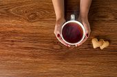 stock photo of black tea  - woman holding hot cup of tea with cookies on wooden table - JPG
