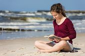 Young woman reading book, sitting on beach