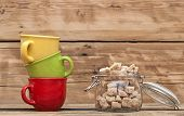 Opened glass jar with sugar with colorful coffee cups on wooden tabletop against grunge wooden backg