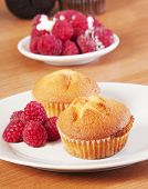 golden muffin with rasberry on white plate