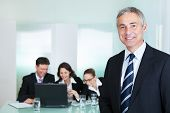 stock photo of leadership  - Corporate promotion and leadership concept with a successful handsome smiling businessman standing in the foreground while his colleagues - JPG