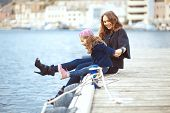 Portrait of mother with her daughter playing on berth near sea in the city, still life photo
