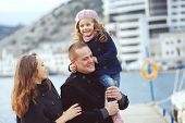Portrait of happy young family walking with their child on berth near sea in the city, still life ph