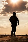 stock photo of soldiers  - Silhouette of young soldier in military helmet against the sun - JPG