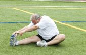 pic of fat-guts  - overweight middle age retired and active senior man stretching his leg muscles after exercising on a sports field outdoors - JPG