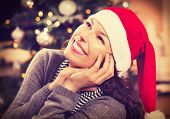 Christmas Woman in Santa Hat. Happy Smiling Girl Celebrating New Year at Home. Christmas Tree