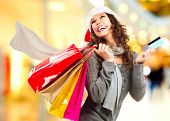 Christmas Shopping. Beautiful Happy Girl With Credit Card and Shopping Bags. Shopping Mall. Shopping