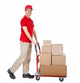 stock photo of politeness  - Cheerful young deliveryman in a red uniform holding trolley loaded with cardboard boxes isolated on white - JPG