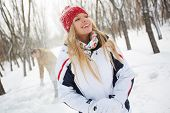 Portrait of happy girl in winterwear laughing on background of her boyfriend in the park