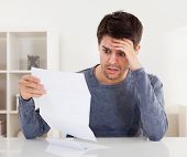 pic of horrifying  - Horrified young man reading a document with an aghast expression and his hand to his forehead as he stares wide eyed at the page of paper - JPG