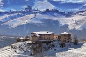 Rural house on the hill and vineyards covered with snow in Piedmont, Northern Italy.