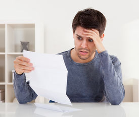 picture of horrifying  - Horrified young man reading a document with an aghast expression and his hand to his forehead as he stares wide eyed at the page of paper - JPG