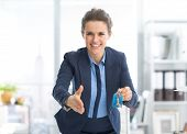 Smiling Realtor Woman With Keys Stretching Hand For Handshake