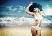 Beautiful young woman in bikini with black strw hat on the beach