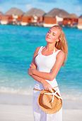 Pretty woman walking along beach on Maldives resort, enjoying summer vacation, freedom and happiness concept
