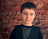 Photo Portrait Of Young Boy With Brick Wall