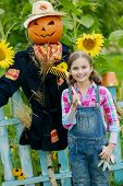 Gardening - Scarecrow and happy girl in the garden