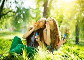Beauty teen girls having fun outdoors. Beautiful joyful teenagers laughing and blowing soap bubbles in spring park. Girlfriends outdoor.