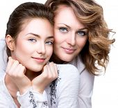 Mother and Teen Daughter. Close-up portrait of attractive happy mother and smiling teenage daughter.