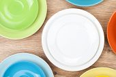 Colorful plates and saucers over wooden table background. View from above