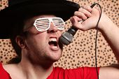 stock photo of crazy hat  - Crazy rock and roller singer with a big black hat - JPG