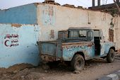 Old SUV in the desert oazis town by the blue building with verses from Koran on the wall
