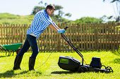 cute man mowing lawn in the backyard of his house