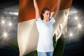 Pretty football fan in white cheering holding ivory coast flag against large football stadium with fans in blue