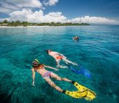 Two ladies snorkeling in the clear tropical sea near the island of Gili Trawangan, Indonesia