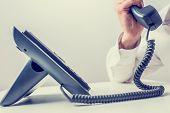 stock photo of telemarketing  - Closeup of businessman making a phone call on landline telephone - JPG