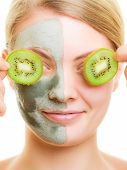 Woman In Clay Facial Mask Covering Eyes With Kiwi