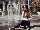 Beautiful teen girl with skateboard. Urban outdoors, teenager's lifestyle. Toned.